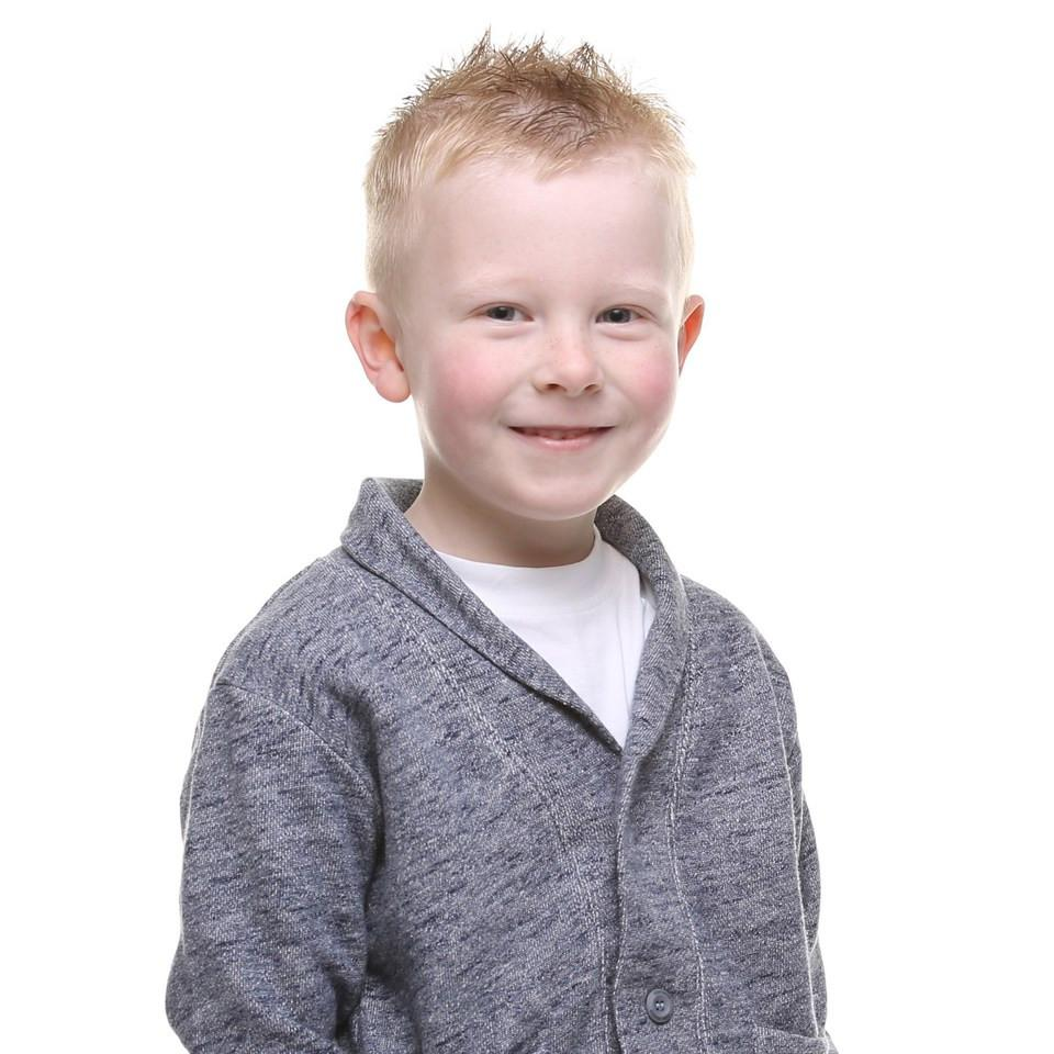 Little boy in front of a white wall