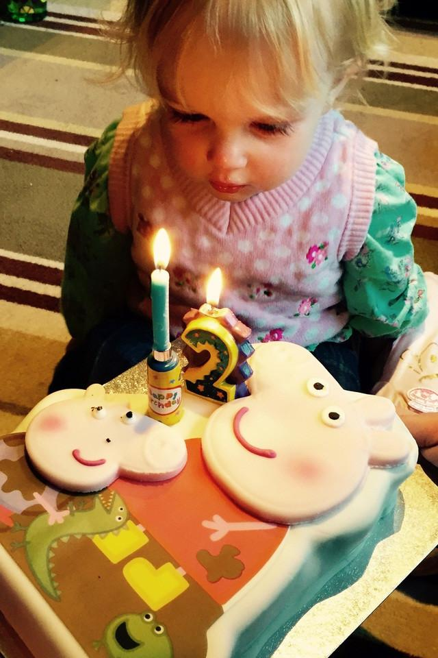 Little girl in front of a cake