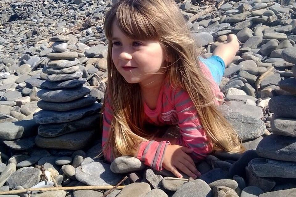 Little blond girl lying on stones