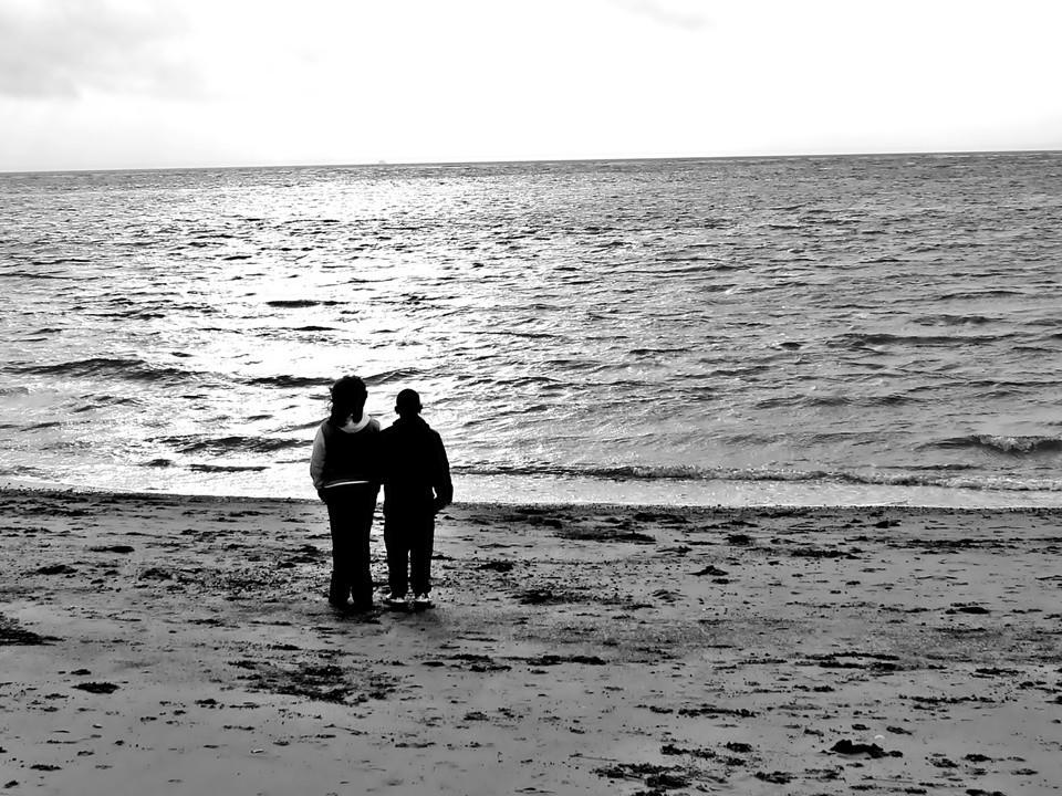 Two peoplestanding in front of the sea