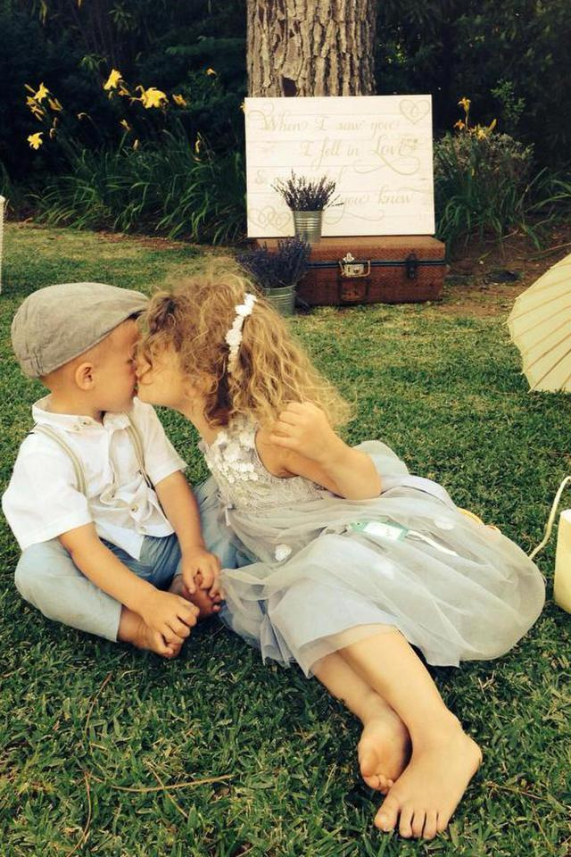 Girl kissing his little brother on the cheek