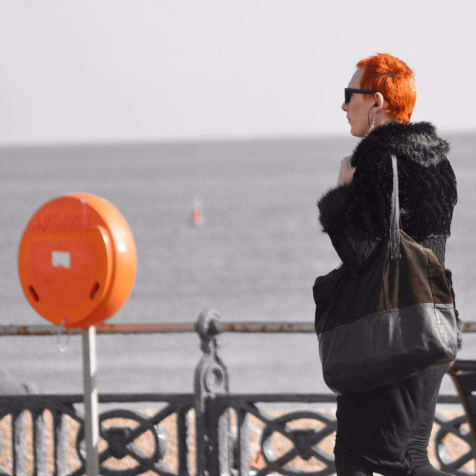 Woman with orange hair standing in front of the beach